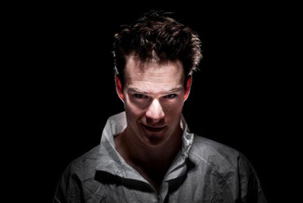 Мужчина с потрепанными волосами выглядывает из темноты и смотрит с ухмылкой