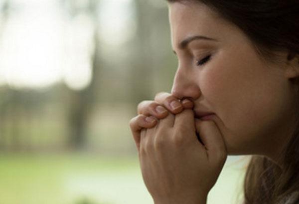 Женщина собирается плакать, держит руки возле лица