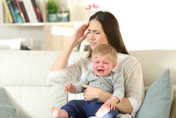 Женщина с плачущим ребенком на руке держится за голову