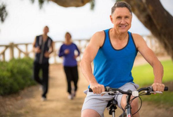 Счастливый мужчина едет на велосипеде. Сзади него бегут парень с девушкой