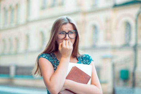 Девушка в очках с бумагами в руке идет по улице и волнуется