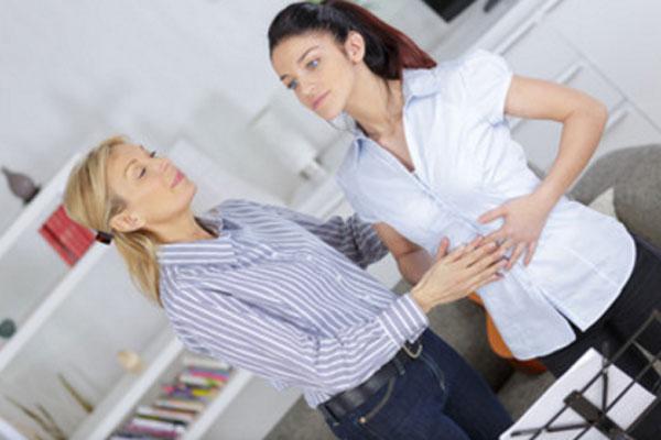 Женщина совершает дыхательные упражнения под присмотром инструктора