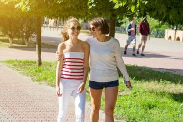 Мама на прогулке вместе с дочерью, обнимает ее