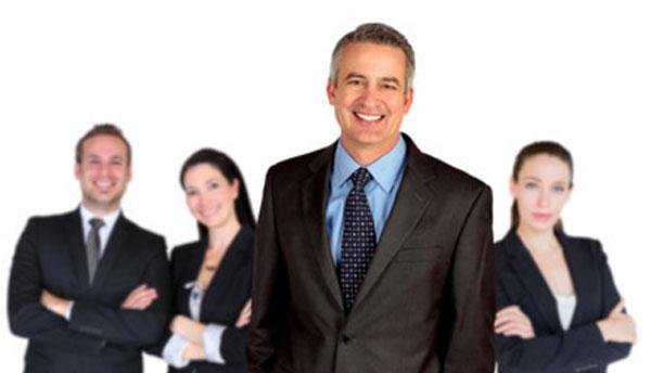 На переднем плане успешный мужчина в костюме, назаднем - две женщины и мужчина тоже в костюмах