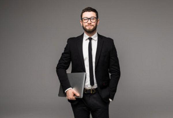 Мужчина в костюме и очках с папкой в руках