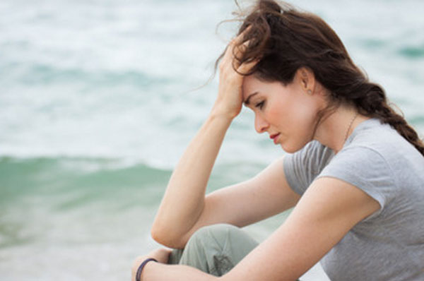 Расстроенная одинокая женщина сидит на берегу