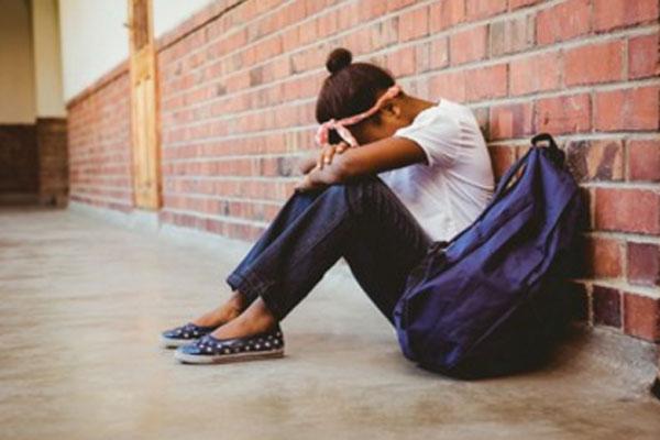 Расстроенная девочка сидит на полу. Рядом с ней школьный рюкзак