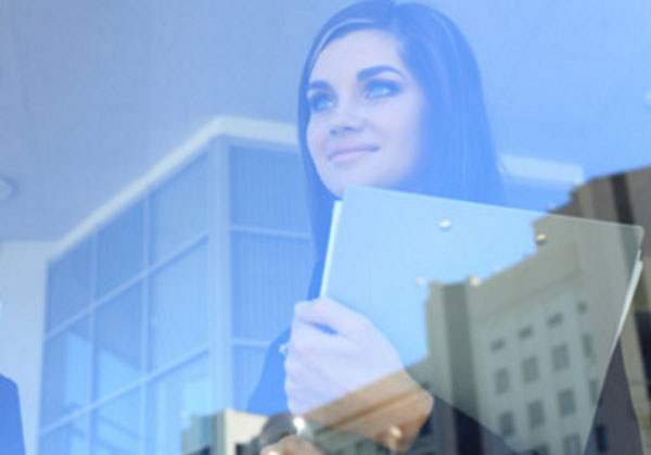 Девушка с папкой в руках стоит у зеркального окна