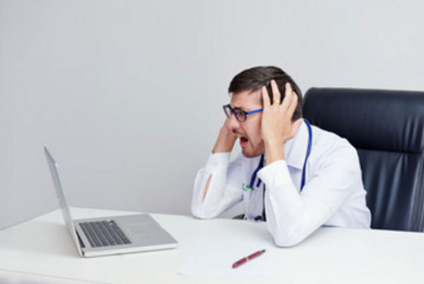 Мужчина в очках сидит перед ноутбуком. У него нервный срыв, он кричит и держится за голову