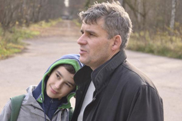 Подросток улыбается, кладет голову на плечо к отцу