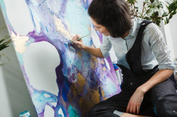 Женщина рисует на холсте