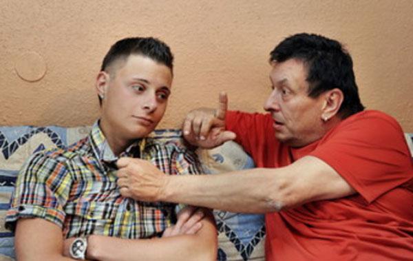 Отец с сыном сидят на диване. Папа хватает подростка за рубашку и что-то ему высказывает