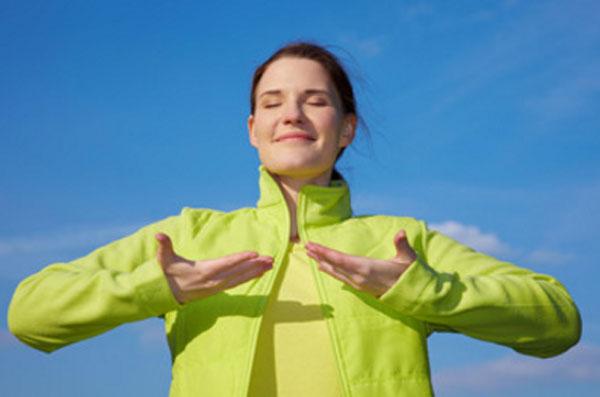 Женщина на улице совершает дыхательные упражнения