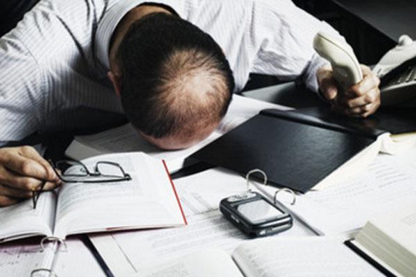 Измученный мужчина положил голову на рабочий стол, засыпанный бумагами по работе