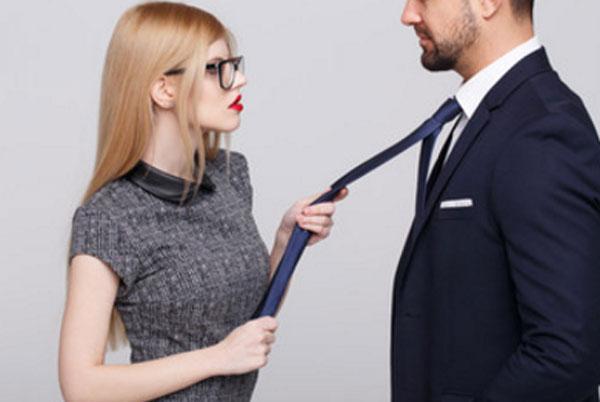 Девушка в очках держит парня в костюме за галстук