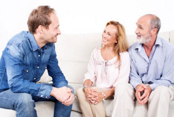 Мужчина сидит на диване с женщиной и пожилым мужчиной. Они общаются