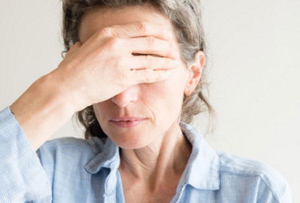 Женщина прикрывает глаза своей рукой