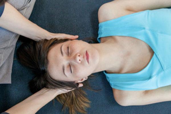 Женщина лежит на кушетке. ей массажируют голову