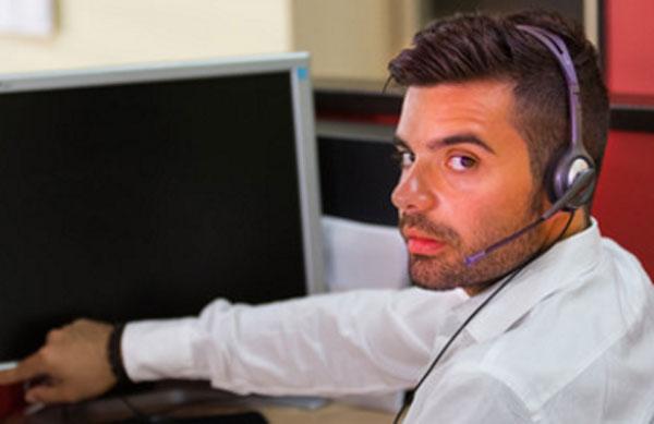 Мужчина с гарнитурой на голове собирается включить компьютер