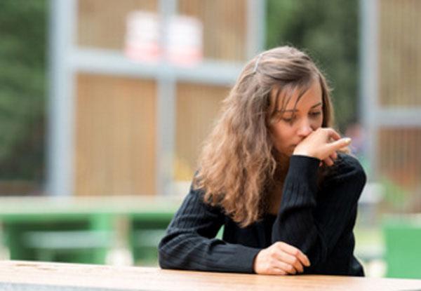 Расстроенная женщина сидит за столом