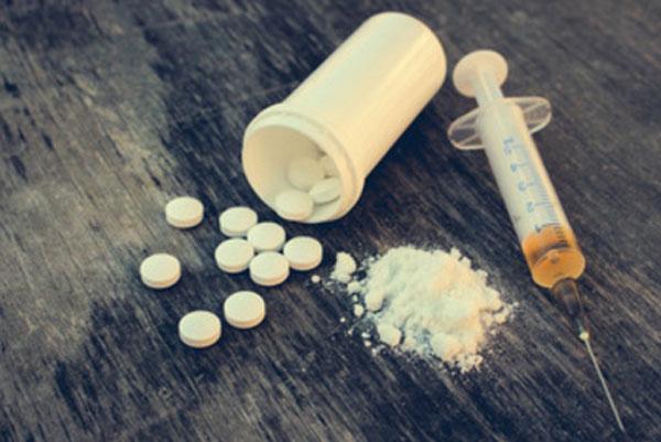 Шприц с жидкостью, флакон с таблетками и рассыпанный порошок