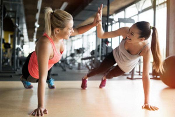 Две девушки держат планку в тренажерном зале
