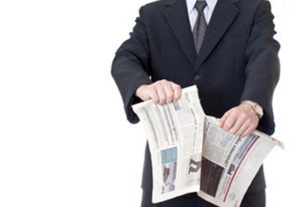 Человек в костюме рвет газету