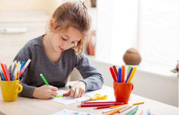 Девочка сидит за столом и что-то рисует