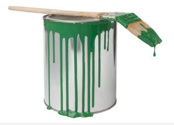 Банка с зеленой краской, на которой лежит кисточка испачканная в зеленой краске