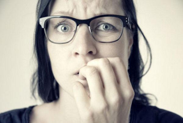 Женщина в очках грызет ногти