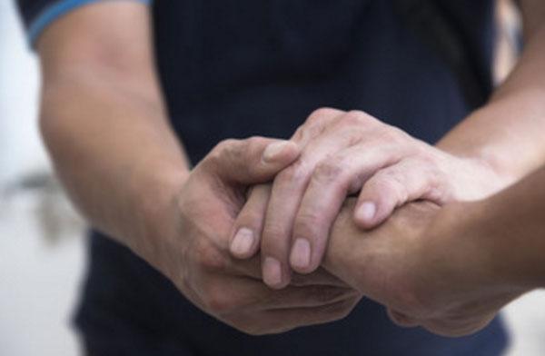 Мужчина держит другого человека за руку