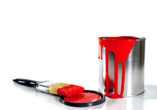 Металлическая банка с красной краской. Рядом лежит кисточка в краске
