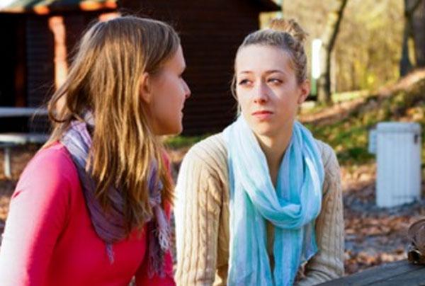 Две девушки сидят на улице. У одной очень грустное лицо