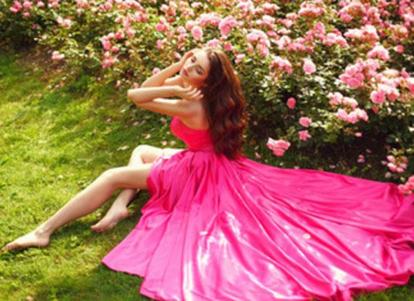 Девушка в вечернем ярко розовом платье сидит на земле возле клумбы с цветами