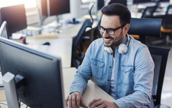 Мужчина работает за компьютером в IT-офисе. Он улыбается