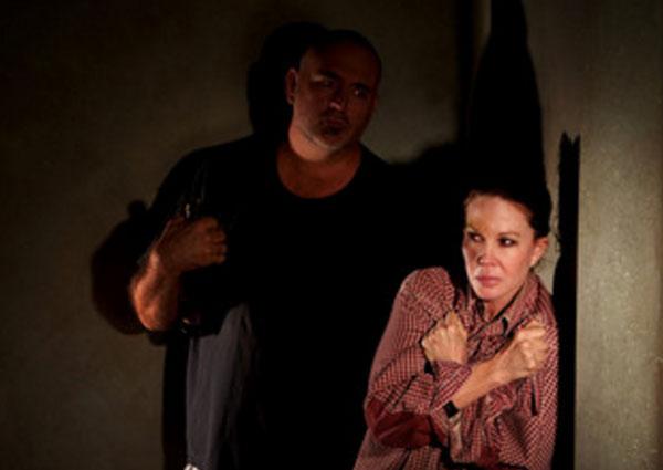 Испуганная женщина стоит возле стены. В комнате темно. сзади здоровый мужик