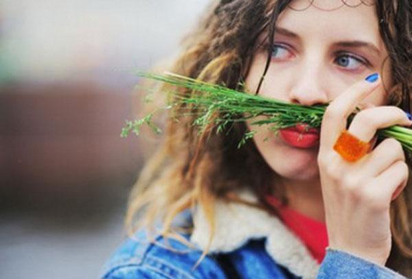Девушка с кольцом из морковки. Держит зелень над губами, представляя, что это усы