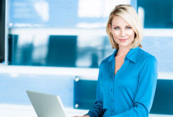 Женщина в светло синей рубашке за ноутбуком