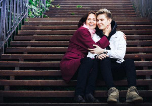 Парень с мамой сидит на ступеньках. Она его обнимает