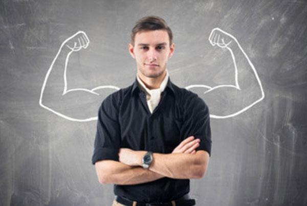 Парень со сложенными перед собой руками. Сзади него доска, на которой нарисованы мускулистые руки