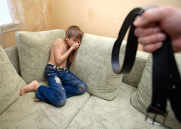 Перепуганный мальчик забился в угол дивана. К нему приближается рука с ремнем