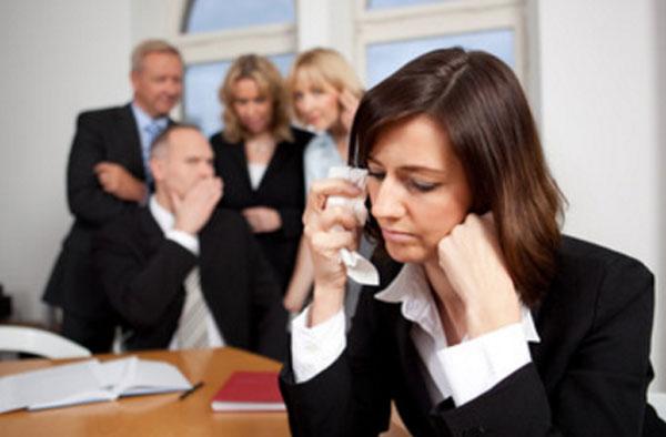 Женщина сидит за столом и плачет. В конце комнаты коллеги, которые ее обсуждают