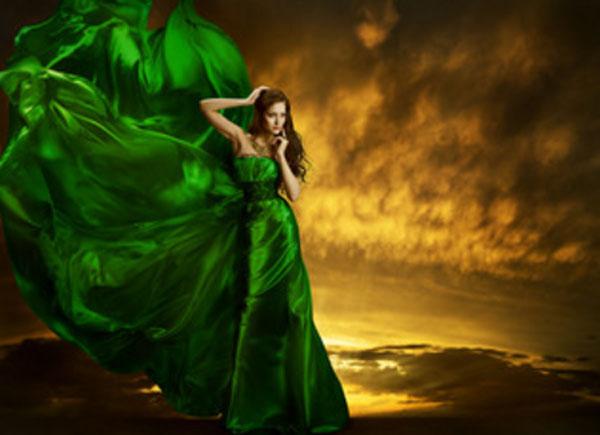 Женщина в зеленом вечернем платье, которое раздувается ветром