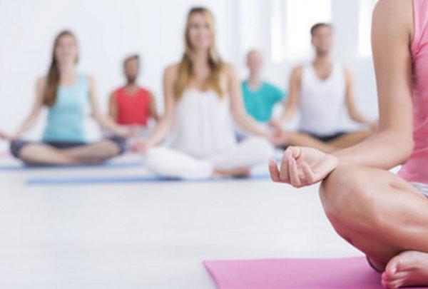 Занятие по медитации. Тренер в розовом и сидит на розовом коврике
