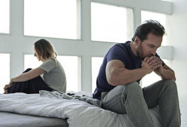 Немолодые мужчина и женщина сидят по разные стороны кровати в задумчивости. У них проблемы в отношениях