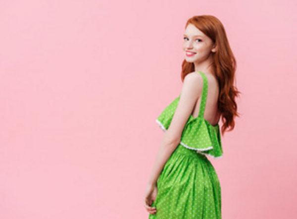 Улыбающаяся девушка в зеленом платье в белый горошек