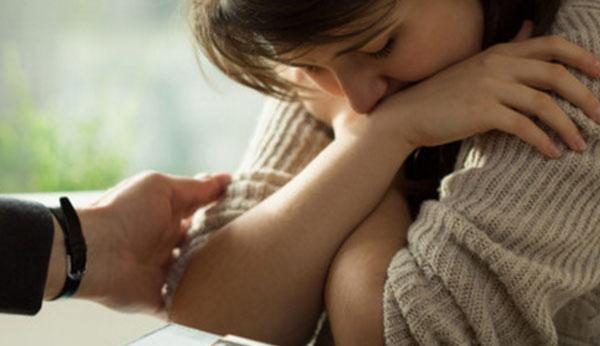 Рука родственника тянется к девушке, у которой депрессия