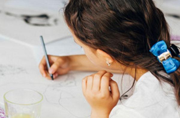 Девочка рисует черным карандашом