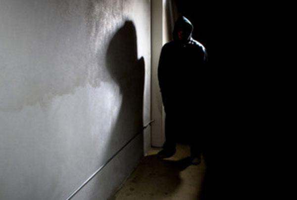 Темный силуэт мужчины в черной комнате