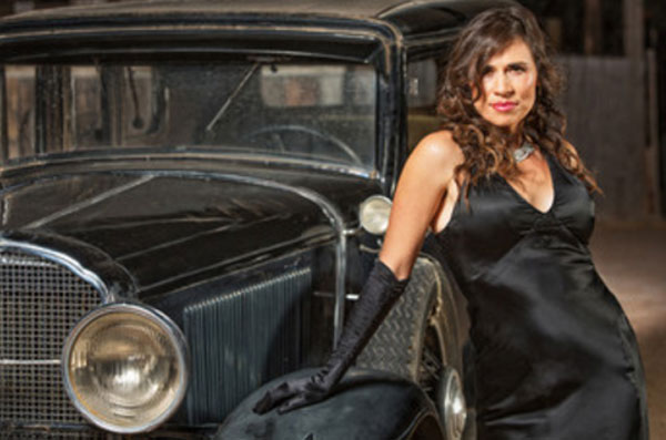 Девушка в черном платье и черных перчатках стоит возле черного ретро автомобиля